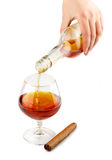 Pouring of cognac with cigar  on white Stock Photography