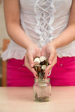 Pouring coins into a jar Royalty Free Stock Image