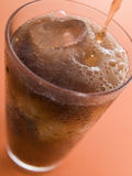 Pouring a Cola into a Glass with Ice Cubes Stock Images
