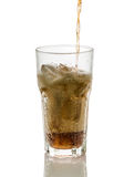 Pouring cola into glass with ice cubes isolated Royalty Free Stock Images