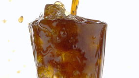 Pouring Cola into a Glass with the Ice Cubes.