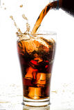 Pouring cola into glass with ice cubes Royalty Free Stock Photos