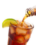 Pouring cola into glass with ice and lime from bottle Stock Photo