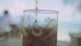 Pouring cola into glass with ices in slow motion on blurred tropical beach background. 1920x1080. Hd stock footage