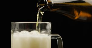 Pouring Cold Light Beer from bottle into a glass. Craft Beer close-up stock photo