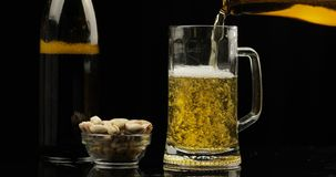 Pouring Cold Light Beer from bottle into a glass. Craft Beer close-up. Black background stock photography