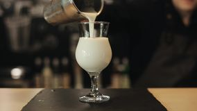 Pouring a cold milkshake from a metal shaker into an empty glass on a bar counter. A close-up of male barista hands pouring milk with ice cubes from a metal stock footage