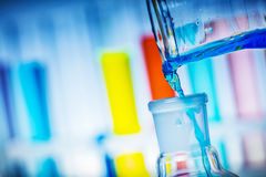 Pouring colorful liquid from tube to a flask. Chemical experiment Stock Photo