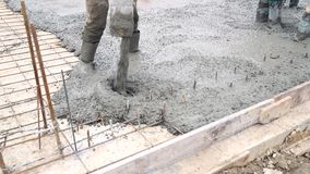 Pouring concrete mix from cement mixer on concreting formwork. A group of workers pouring concrete on a construction.  stock video footage