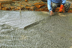 Pouring concrete mix for road construction workers. Stock Images
