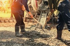 Pouring concrete with worker mix cement at construction. Site Royalty Free Stock Image