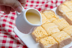 Pouring condensed milk on toasts with butter Stock Photos