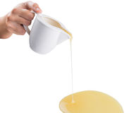 Pouring Condensed Milk VI. Female hand pouring condensed milk over white background royalty free stock photo