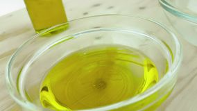 Pouring cooking olive oil in the bottle in the white container with drops on wood table background near olive oil bottle stock footage