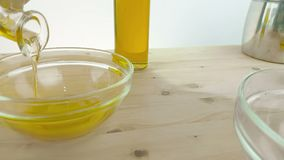 Pouring cooking olive oil in the bottle in the white container on wood table background near olive oil bottle, shot in slow motion stock video footage