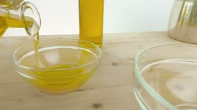 Pouring cooking olive oil in the bottle in the white container on wood table background near olive oil bottle, shot in slow motion stock footage