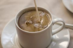 Pouring cream. Cream being poured into coffee Stock Image
