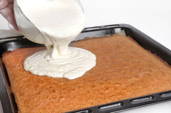 Pouring cream on cake Stock Images