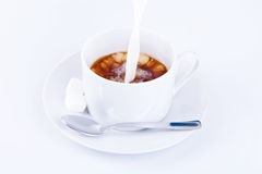 Pouring cream into a cup of coffee Royalty Free Stock Photos