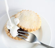Pouring cream on a mince pie Royalty Free Stock Images