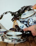 Pouring a cup of tea in a teapot Royalty Free Stock Photography