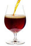 Pouring dark ale beer into a tulip glass  isolated Royalty Free Stock Photography