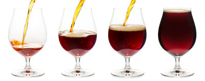 Pouring dark ale beer into a tulip glass isolated Stock Image