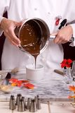 Pouring Dark Chocolate. Close up capture of a uniformed Pastry Chef pouring hot dark chocolate from a sauce pan into a bowl Royalty Free Stock Images