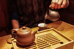 Pouring dark pu-erh tea from a purple clay jar into a small tasting cup royalty free stock photo
