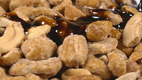 Pouring delicious chocolate syrup over mixed nuts stock video footage