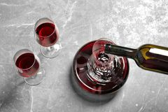 Pouring delicious red wine into decanter on grey table,. Above view Stock Photography
