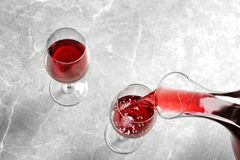 Pouring delicious red wine into glass. On grey table, above view royalty free stock images