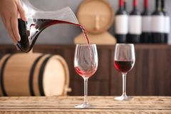 Pouring delicious red wine into glass. On table royalty free stock images