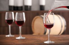 Pouring delicious red wine into glass. On table stock photos