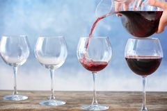 Pouring delicious red wine into glass. On table stock images