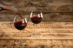 Pouring delicious red wine into glass. On table royalty free stock photography