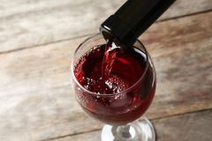Pouring delicious red wine into glass. On wooden background stock images