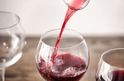 Pouring delicious red wine into glass on table. Closeup stock image