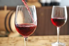 Pouring delicious red wine into glass on table. Closeup royalty free stock image