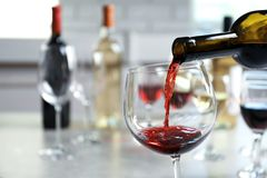 Pouring delicious red wine into glass on table. Tasting royalty free stock images