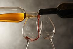 Pouring different wines from bottles into glasses. On dark background royalty free stock images