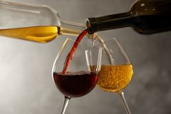 Pouring different wines from bottles into glasses. On dark background royalty free stock photos