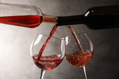 Pouring different wines from bottles into glasses. On dark background royalty free stock image
