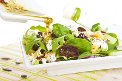 Pouring dressing on fresh salad. Royalty Free Stock Image