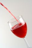 Pouring a drink. Pouring a sparkling red drink into a glass Royalty Free Stock Image