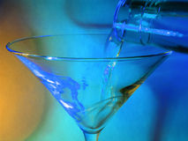 Pouring a drink. Into a martini glass. Focus in plane of pour which is motion blurred (compare left and right side of rim royalty free stock photo