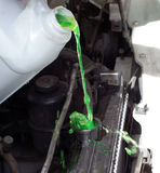 Pouring engine coolant into a car. Green-colored coolant being into a vehicle's radiator Stock Image