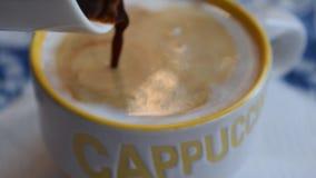 Pouring espresso coffee in a cappuccino cup stock video