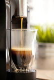 Pouring Espresso coffee into a cup. Filling a clear glass cup with fresh espresso coffee with a crema layer Royalty Free Stock Photography
