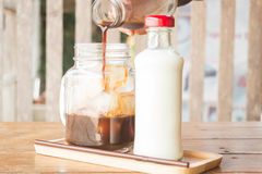 Pouring espresso to iced glass of coffee Stock Photos